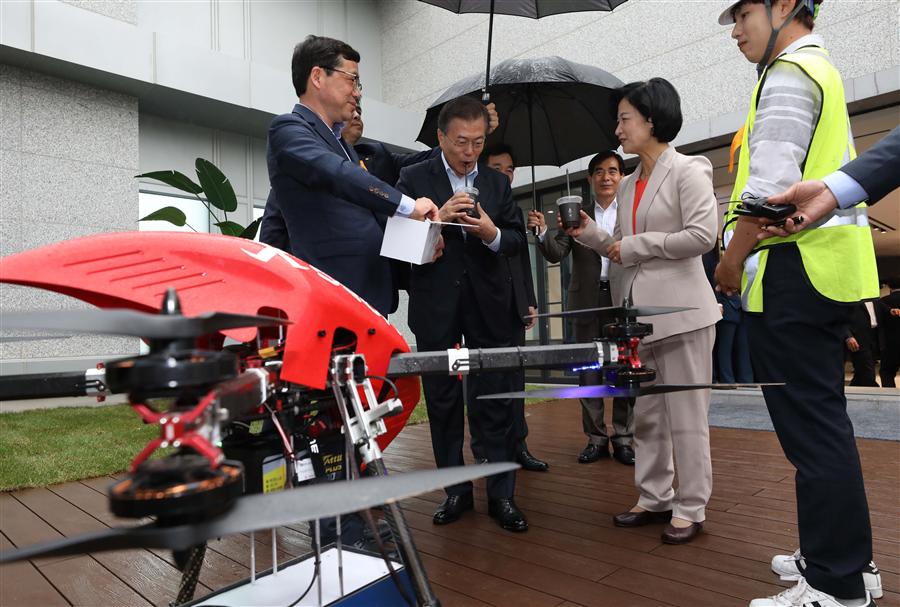 문재인 대통령이 17일 서울 마곡 R&D 단지에서 열린 혁신성장 점검회의에 앞서 사전 환담 중 드론이 운반한 커피음료를 받고 마시고 있다. 사진/뉴시스